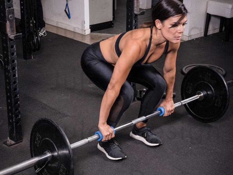 Woman lifting barbell with fatgripz